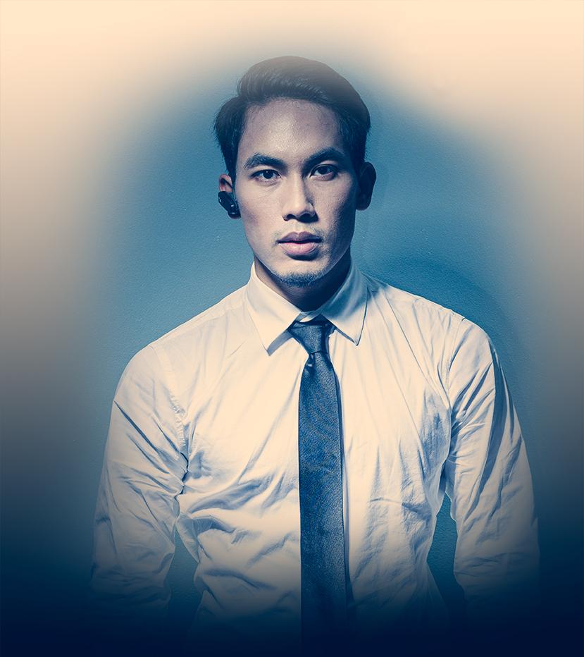 David Khum est le dirigeant de l'agence de sécurité Secupro. Il est habillé d'une chemise blanche et d'une cravate noire et il porte une oreillette à son oreille droite.