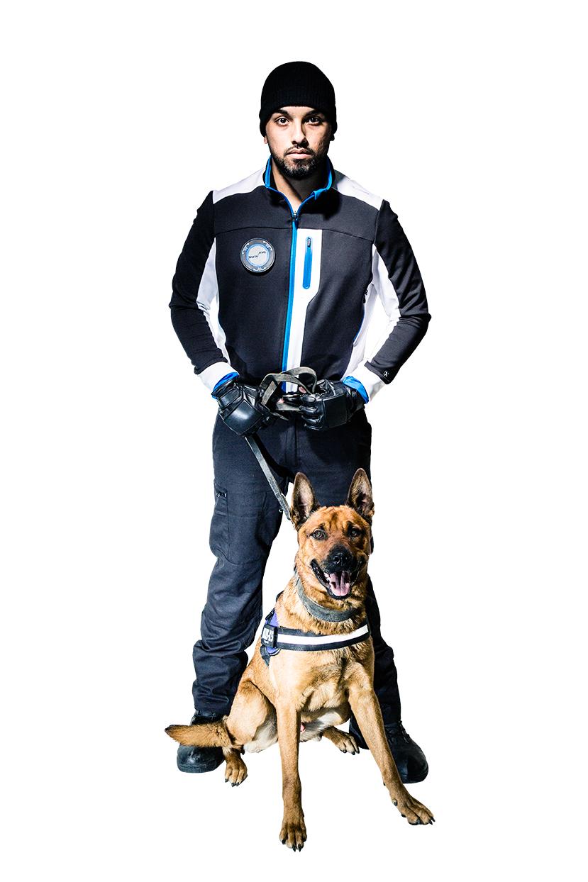 Un agent cynophile en tenue noire tient en laisse un chien assis de race malinois de couleur fauve avec la gueule ouverte.