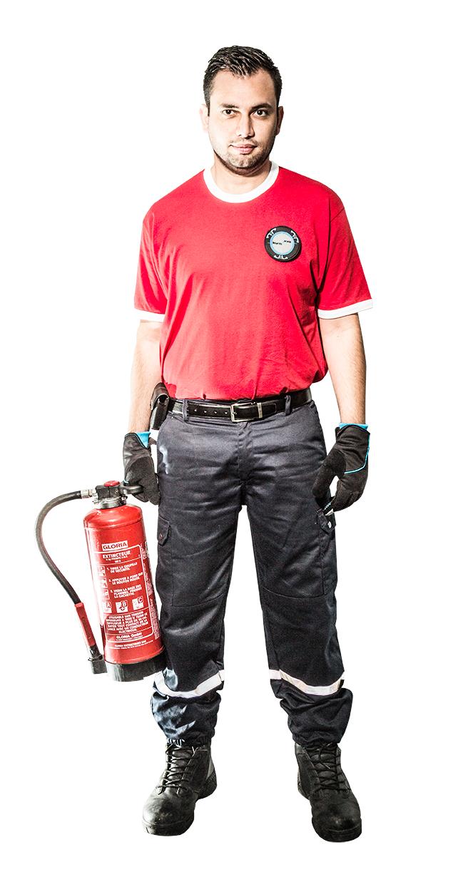Un agent incendie SSIAP 1 tient avec ses gants un extincteur de feu. Il est habillé d'un t-shirt rouge vif, d'un pantalon réfléchissant et de chaussure de sécurité de marque magnum.